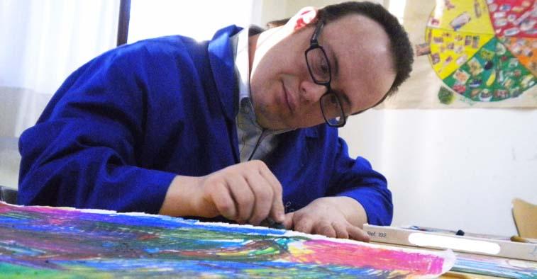 Imagen de adulto con sindrome de down pintando