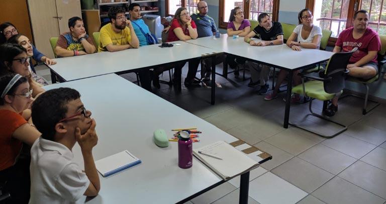 Foto del aula donde los Representantes del colectivo de personas con discapacidad reciben formación. En la Foto aparecen las 14 personas de la Asociación AMP sentadas atendiendo a las explicaciones.