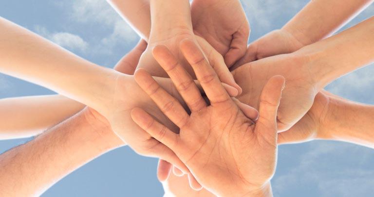 manos unas sobre otras
