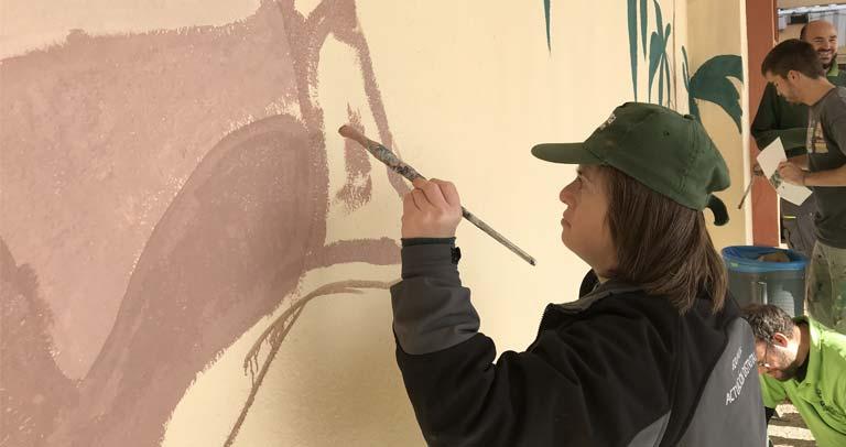 TRABAJADORA pintando el mural