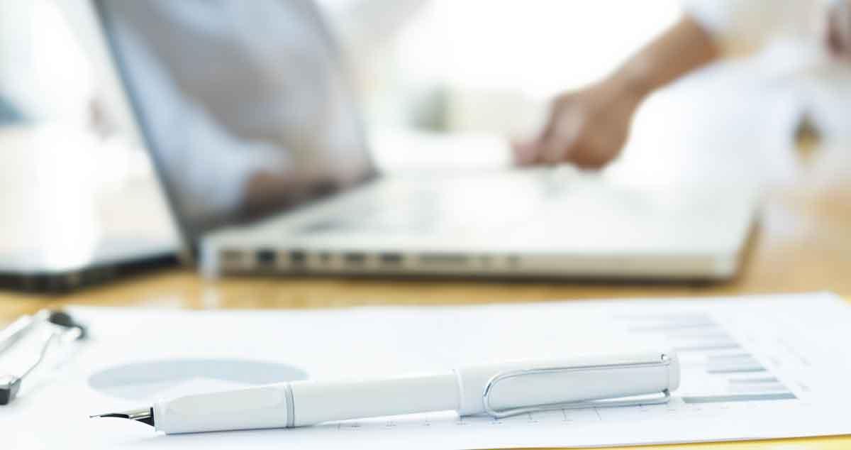 ordenador y pluma sobre papel