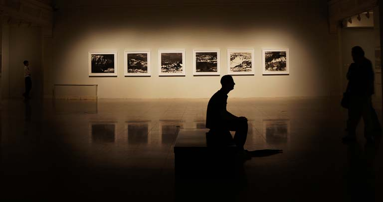 una persona sentada en una sala de exposiciones